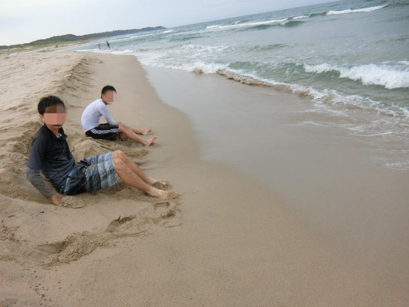 砂浜に座り海を堪能している息子達