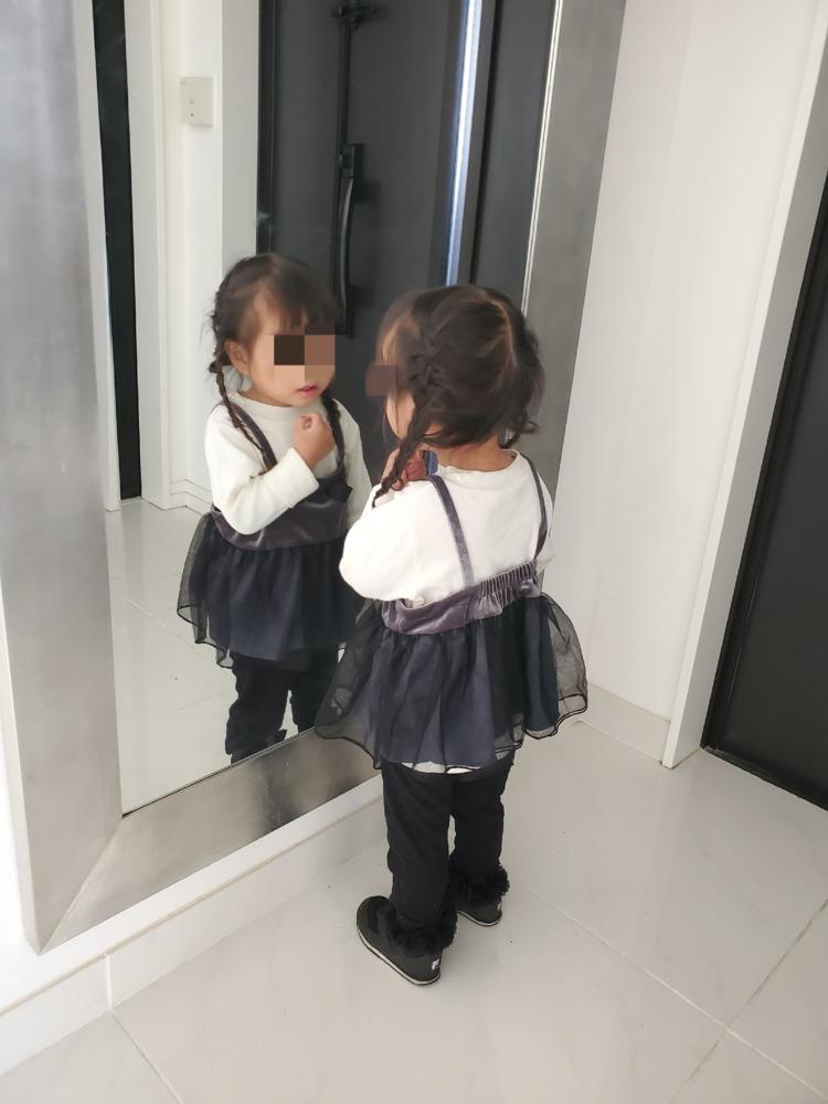 玄関で鏡チェックをする娘