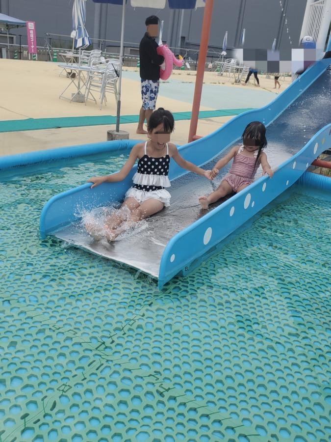 プールの滑り台で滑っている子供達